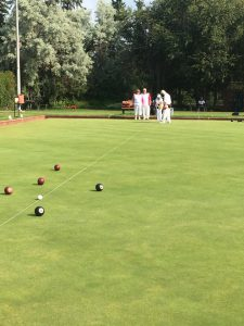 Lawn bowls with players in the background
